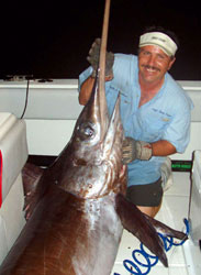 A happy guest with a broadbill swordfish