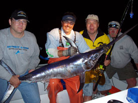 Four clients posing with their swordfish